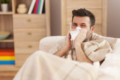 Sick man. Man blowing his nose while lying sick in bed Royalty Free Stock Photography