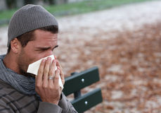 Sick man blowing nose. Sick man with a cold blowing nose Stock Photography