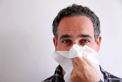 Sick man blowing nose stock images