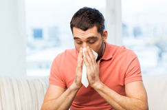 Sick man blowing nose to paper napkin at home Royalty Free Stock Photos