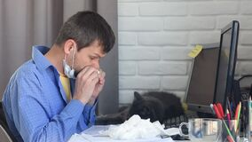 A sick man blows his nose in a handkerchief, working remotely on quarantine