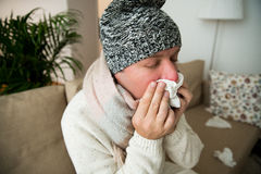 Sick man catch cold. Ill person sneezing, coughing, got flu, having red runny nose, spraying medication. Sitting at home on couch Stock Photos