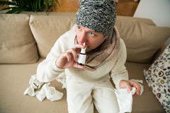 Sick man catch cold. Ill person sneezing, coughing, got flu, having red runny nose, spraying medication. Sitting at home on couch Royalty Free Stock Photography