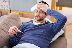Sick man checking his temperature Stock Image