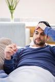 Sick man checking his temperature Royalty Free Stock Photo