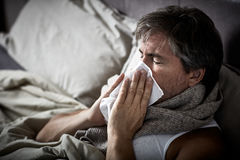 Sick man with cold lying in bed and blow nose. royalty free stock images