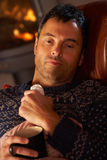 Sick Man With Cold Resting On Sofa. By Cosy Log Fire Royalty Free Stock Photo