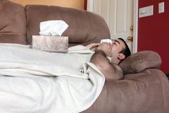 Sick Man on the Couch. A young adult sick on the couch at home blows his nose with a tissue Stock Photos