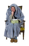 Sick Man With Cough, Cold, Flu Isolated. A sick man with a cough, cold, or flu is ill and sits in a chair with a box of his kleenix facial tissue. The male use Royalty Free Stock Photos