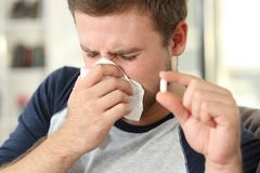 Sick man coughing and holding a pill Stock Photography