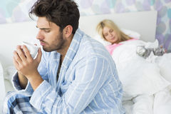 Sick man drinking coffee on bed while woman sleeping in background at home Royalty Free Stock Photography