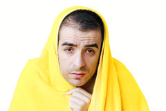 Sick man with fever. Sad sick man with fever in a yellow blanket Royalty Free Stock Photography