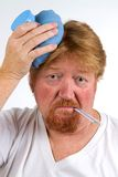 Sick Man With Flu. Sick man with thermometer in mouth and hot water bottle on head has the flu Stock Photos