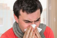 Sick man with flu or cold sneezing into handkerchief. Cold and flu concept Stock Photos
