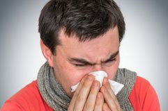 Sick man with flu or cold sneezing into handkerchief Royalty Free Stock Photos