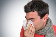 Sick man with flu or cold sneezing into handkerchief Stock Photos