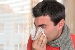 Sick man with flu or cold sneezing into handkerchief. Cold and flu concept Stock Image