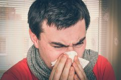 Sick man with flu or cold sneezing into handkerchief. Cold and flu concept - retro style Royalty Free Stock Photography