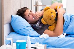 The sick man with flu lying in the bed Stock Images