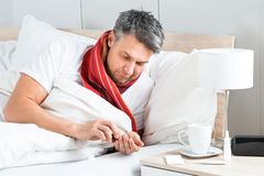 Sick man having medicine in bed Royalty Free Stock Photography