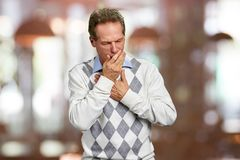 Sick man having severe infection. Mature man suffering from cough attack on blurred background. Man has a flu royalty free stock image