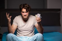 The sick man in his bed with medicines. Sick man in his bed with medicines royalty free stock images