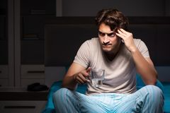The sick man in his bed with medicines. Sick man in his bed with medicines royalty free stock photography