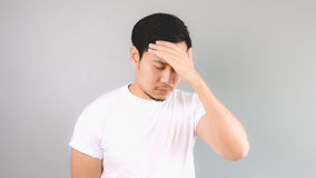 A sick man with his hand covering his foehead. An asian man with white t-shirt and grey background stock photo