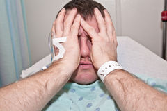 Sick Man in Hospital. Sick man in a hospital bed feeling pain and stress stock photography