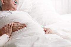 Sick man in hospital. Sick senior men laying in hospital bed Stock Image