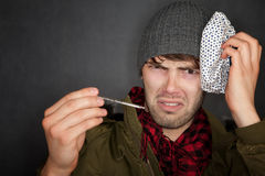 Sick man with ice pack and thermometer Royalty Free Stock Image