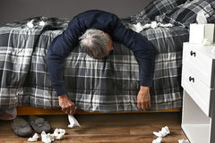 Sick Man Lying Across Bed Royalty Free Stock Images