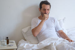 Sick man lying on bed and coughing. A lot Stock Photography
