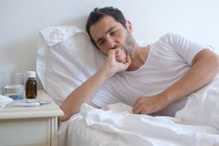 Sick man lying on bed and coughing Stock Photography