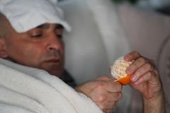 Eating an orange to assume vitamin C. Sick man lying in bed eating an orange to get vitamin C. Selective focus stock photo