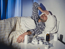 Sick man lying in bed with headache suffering cold and winter flu virus Royalty Free Stock Image