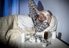 Sick man lying in bed with headache suffering cold and winter flu virus Royalty Free Stock Images