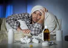 Sick man lying in bed with headache suffering cold and winter flu virus. Sick wasted man lying in bed suffering cold , headache and winter flu virus having lots Royalty Free Stock Photo
