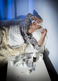 Sick man lying in bed with headache suffering cold and winter flu virus Stock Photos