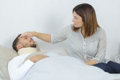 Sick man lying in bed at hospital and wife. Sick men lying in bed at hospital and his wife stock photography