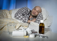 Sick man lying in bed suffering cold and winter flu virus having medicine and tablets. Sick wasted man lying in bed at home wearing pajama suffering cold and Stock Photos