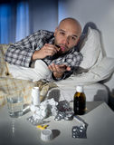 Sick man lying in bed suffering cold and winter flu virus having medicine and tablets. Sick wasted man lying in bed at home wearing pajama suffering cold and Stock Image
