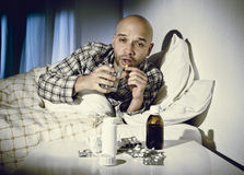 Sick man lying in bed suffering cold and winter flu virus having medicine and tablets Stock Photo