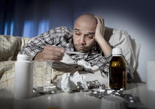 Sick man lying in bed suffering cold and winter flu virus having medicine and tablets. Sick wasted man lying in bed wearing pajama suffering cold and winter flu Royalty Free Stock Photos