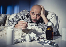 Sick man lying in bed suffering cold and winter flu virus having medicine and tablets Royalty Free Stock Images