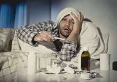 Sick man lying in bed suffering cold and winter flu virus having medicine and tablets. Sick wasted man lying in bed wearing pajama suffering cold and winter flu Stock Image