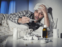 Sick man lying in bed suffering cold and winter flu virus having medicine and tablets. Sick wasted man lying in bed wearing pajama suffering cold and winter flu royalty free stock images
