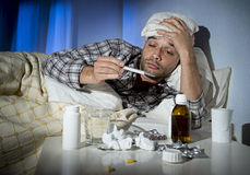 Sick man lying in bed suffering cold and winter flu virus having medicine and tablets. Sick wasted man lying in bed wearing pajama suffering cold and winter flu Stock Photography