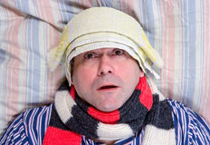 Sick man lying in bed. Sick man with towel on forehead lying in bed Stock Photos