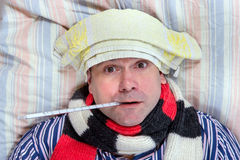Sick man lying in the bed. Sick man with towel on his forehead lying in the bed Royalty Free Stock Photography